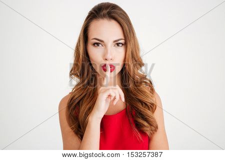 Portrait of a young woman in red dress showing silence gesture with finger over lips isolated on a white background