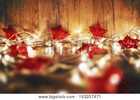 Merry Christmas and Happy Holidays! Red stars and Christmas garland lights on old dark wooden rustic background.
