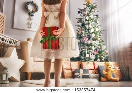 Merry Christmas and Happy Holidays! Cheerful cute little child girl with present. Kid holds a gift box near Christmas tree indoors.