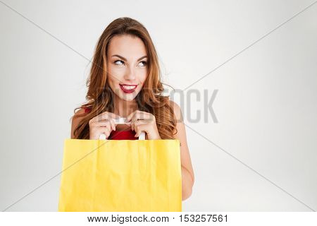 Portrait of a charming pretty woman holding yellow shopping bag and looking away isolated on a white background