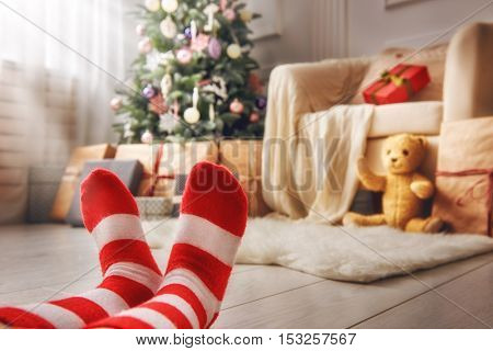 Merry Christmas and Happy Holidays! Cute little feet of child. Kid sitting near Christmas tree indoors.