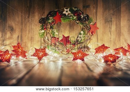 Merry Christmas and Happy Holidays! Red stars, decorative wreath and Christmas garland lights on old dark wooden rustic background.