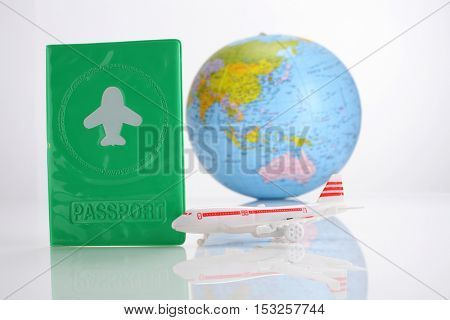 traveling concept,passport globe and toy airplane on the white background
