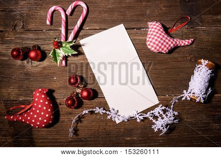 White paper for Christmas greeting card and ornaments on a wooden table