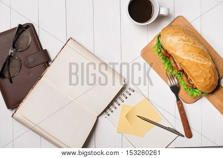 Snack at break time. Healthy business lunch in office top view of Vietnamese sandwich or Ban Mi on white wooden desk with coffee mobile phone and notepad with pen flat lay.
