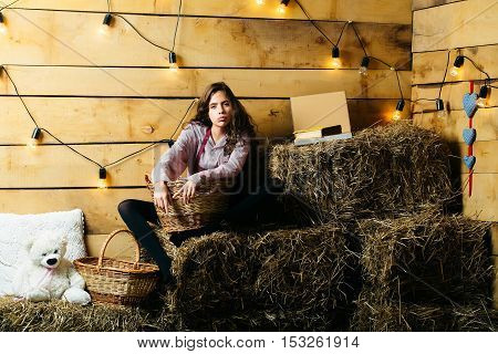 Pretty girl teenager young woman cookee helper in apron sits on straw bales with wicker baskets on rustic background