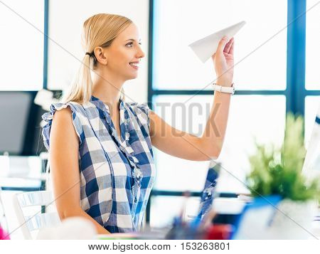 Young woman working in office holding paper plane