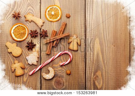 Christmas food decoration with gingerbread cookies, spices and candies. View from above on wooden background with copy space