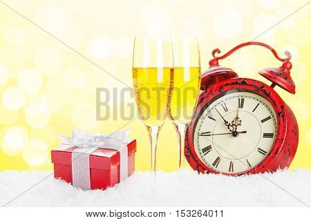 Champagne, gift box and christmas clock with bokeh background