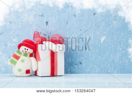 Christmas background with gift box and snowman in front of stone wall with copy space