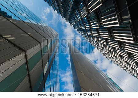 Tall skyscraper office buildings with cloudy and blue sky above