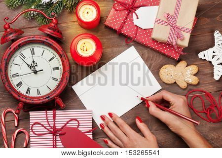 Female writing christmas greeting card and gift wrapping above wooden table. Top view with copy space