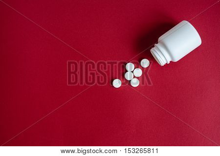 tablets in plastic container on red background top view