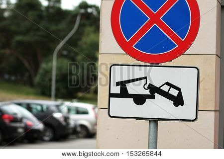 road sign - no parking and cars will be towed away and parked cars in the background