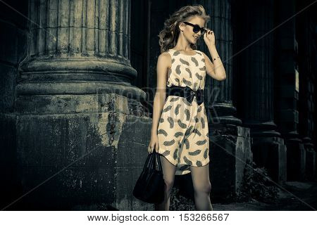 Happy fashionable woman walking in the city. Fashion shot outdoor.
