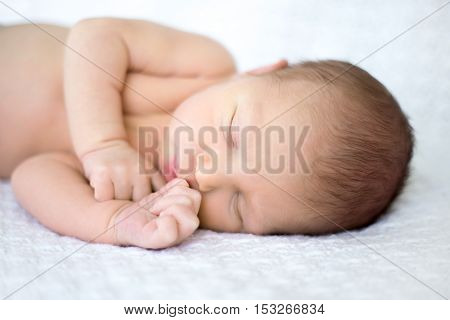 Close-up portrait of sweet newborn infant sleeping quietly on bed on white blanket with little hands lying near mouth