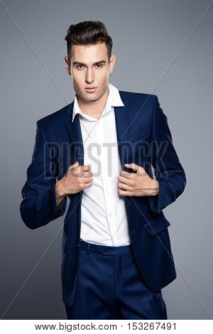 Vogue shot of a handsome male model in elegant classic suit. Men's beauty, fashion.