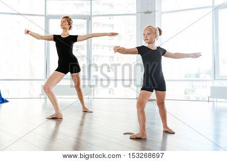 Cute little girl ballerina dancing with her teacher in dance studio