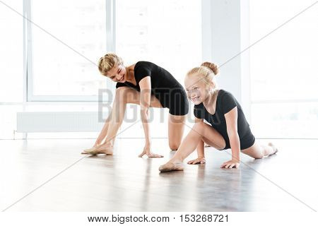 Cheerful little beautiful ballerina and her teacher stretching on the floor in ballet school
