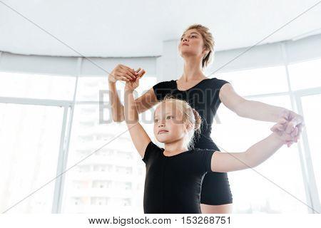 Beautiful little ballerina learning dancing with teacher in dance studio