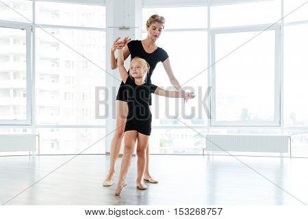 Beautiful little ballerina and her teacher dancing in ballet school
