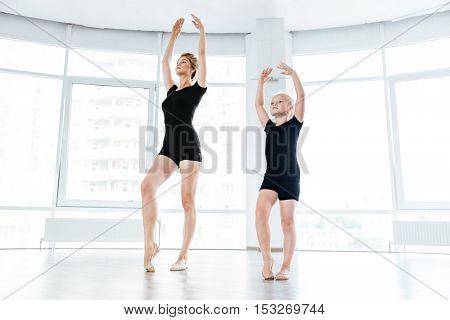 Full length of little girl ballerine and her teacher dancing in ballet class