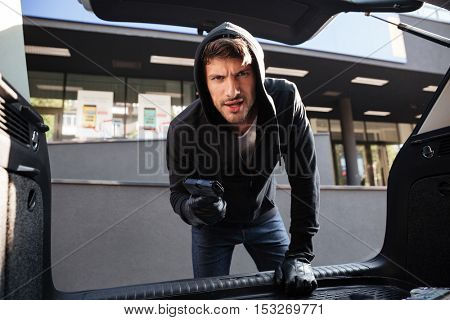 Furious criminal man in hoodie threatening with gun and looking at car trunk