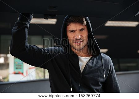 Angry criminal man in hoodie closing car trunk outdoors