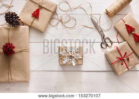 Gift wrapping. Packaging modern christmas present. Lots of gift boxes in craft paper, decorated with red satin ribbon bows and twine. Christmas and winter holidays concept, top view, copy space