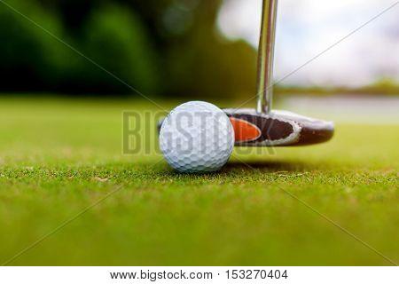 Putter hitting a golf ball on the green