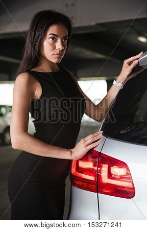 Closeup of pretty young woman in black dress standing near her car