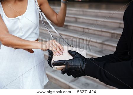 Closeup of criminal man in gloves stealing woman bag outdoors