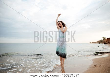 Smiling beautiful young woman in dress dancing on the beach