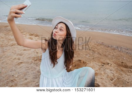 Funny playful young woman taking selfie with cell phone on the beach