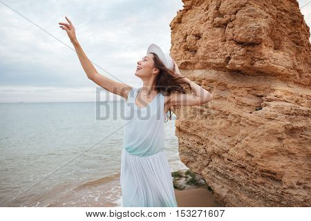Smiling beautiful young woman standing with raised hand near the rock on the beach
