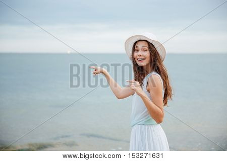 Happy lovely young woman in white hat and dress smiling and pointing away on the beach