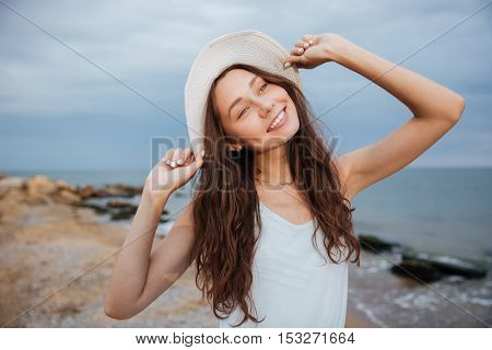 Portrait of smiling cute young woman in hat on the beach