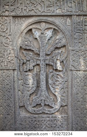 Close up shot of a cross carved in a stone.