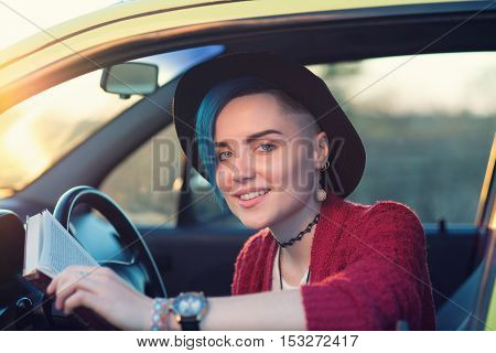 Stylish student girl reading book in car