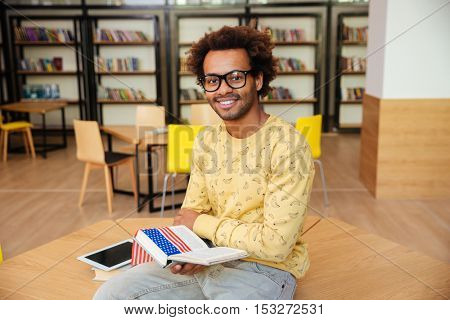 Closeup of happy attractive african young man in glasses studying in library