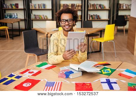 Happy african american young man in glasses with tablet and flags of diffrent countries sitting in library