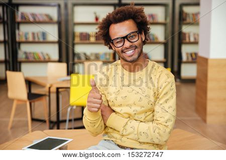 Smilng african young man winking and showing thumbs up in library
