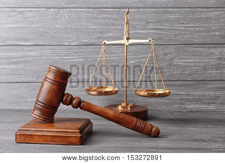 Judge's gavel and scales on wooden wall background