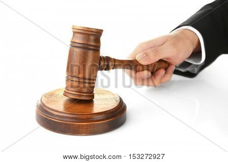 Judge's hand holding gavel on white background