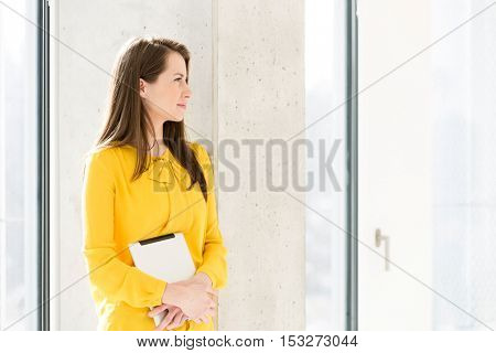 Thoughtful young businesswoman holding digital tablet while leaning on wall in new office