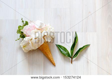 bouquet of pink peonies in waffle cup onwooden floor