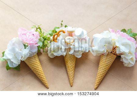bouquets of peonies in a waffle cone on craft paper top view