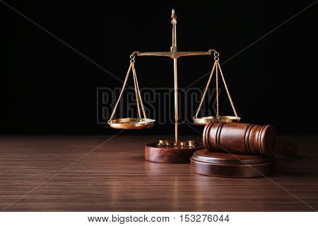 Justice scales and judges gavel on wooden table and black background