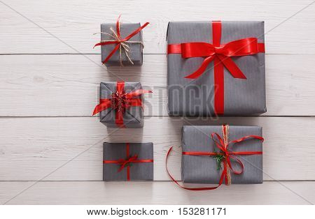 Lots of gift boxes on white wood background. Stylish modern presents in gray paper decorated with red satin ribbon bows. Christmas and winter holidays concept, top view, flat lay, copy space
