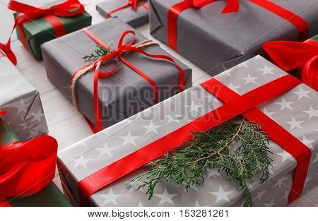 Lots of gift boxes on white wood background. Stylish modern presents in gray paper decorated with red satin ribbon bows and fir tree branch. Christmas and winter holidays concept.